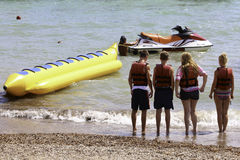 Holiday fun on banana boat. Tourists about to be having fun being pulled on a banana boat Royalty Free Stock Image