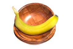 Banana In A Bowl. A fresh banana sitting in a wooden bowl, at the top of a stack of bowls, isolated against a white background Stock Photo