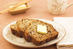 Banana bread. Freshly baked banana bread slices with butter and mug of tea in horizontal format Royalty Free Stock Photography