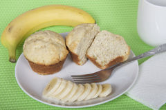 Banana bread muffins on a plate with a fork and sliced banana wi. Th napkin and mug of milk. Whole banana on place mat behind plate. Festive green placemat Stock Photography