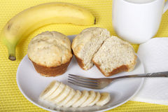 Banana bread muffins on a plate with a fork and sliced banana wi. Th napkin and mug of milk. Whole banana on place mat behind plate. yellow festive placemat Stock Photos