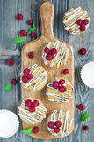 Banana bread muffins with raspberries, cherries, white chocolate, top view. Banana bread muffins with raspberries, cherries and white chocolate on wooden board Royalty Free Stock Photography