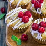 Banana bread muffins with raspberries, cherries and white chocolate on wooden board, square format. Banana bread muffins with raspberries, cherries and white Royalty Free Stock Photos