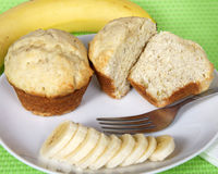 Banana bread muffins on a white plate with sliced bananas and fo. Rk on the plate, whole banana in background on green place mat, closeup Stock Photography