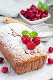 Banana bread with raspberries, cherries and white chocolate, vertical. Banana bread with raspberries, cherries and white chocolate on parchment, vertical Stock Image