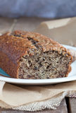 Banana bread in the baking paper on the wooden table Royalty Free Stock Photo