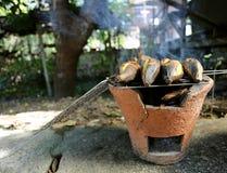 Banana burning with peel on old terracotta pot stock image