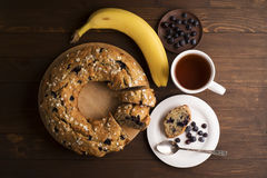 Banana cake with blueberries and cereal. Laid out on a Board with a tea set, bananas and blueberries on wooden table Stock Images