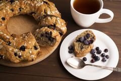 Banana cake with blueberries and cereal. Laid out on a Board with a tea set, bananas and blueberries on wooden table Stock Image
