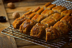 The banana cake with walnuts and maple syrup cut with slices on a wooden table. Stock Photos