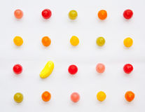 Banana and candies. Aligned candies and one banana in rectangle geometry royalty free stock photography