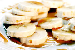 Banana And Caramel Sauce. Banana in slices with caramel sauce on a white plate Stock Image