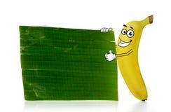 Banana cartoon character. Stands beside a plain banana leaf Stock Images