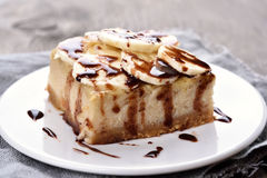 Banana cheese cake. Cheese cake with chocolate syrup and piece of banana Royalty Free Stock Photography