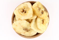 Banana chips in a wooden circular shape. Banana chips in a wooden round shape on white background Stock Photo
