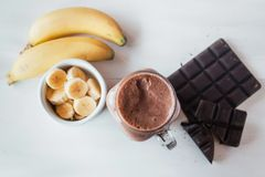 Banana and chocolate smoothie in the glass jar milkshakes, natural and organic drink royalty free stock photography