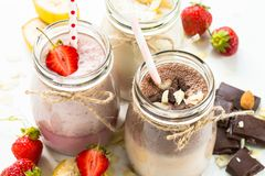 Banana chocolate and strawberry milkshakes royalty free stock images