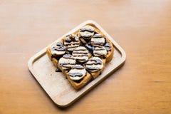Banana com chocolate no pão grelhado no prato de madeira Fotografia de Stock