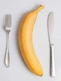 Banana com forquilha e faca Imagem de Stock Royalty Free
