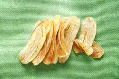 Banana cortada dourada fritada friável na esteira líquida verde imagens de stock royalty free
