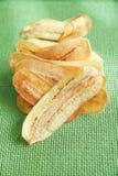 Banana cortada dourada fritada friável na esteira líquida verde Fotografia de Stock