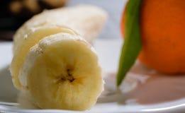 Banana cortada em uma placa branca com a tanjerina no backg imagens de stock royalty free