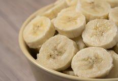 Banana cortada na bacia cerâmica no fundo de madeira Fim acima fotografia de stock royalty free