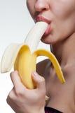 Banana cortante da jovem mulher fotografia de stock royalty free