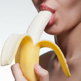 Banana cortante da jovem mulher isolada no branco fotografia de stock