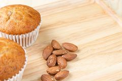 Banana cup cake and roasted almonds are placed on wooden floors royalty free stock photo