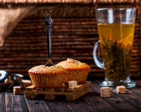 Banana cupcake with a spoon. Transparent Cup with green tea Royalty Free Stock Photo