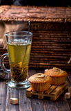 Banana cupcake on a wooden stand. Transparent Cup with green tea Royalty Free Stock Image