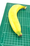 Banana on cutting mat. On white background Stock Images