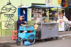 Banana-da-terra da repreensão da mulher na rua em Banos, Equador fotografia de stock
