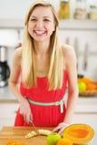 Banana de sorriso do corte da jovem mulher na cozinha Fotos de Stock