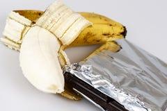 Banana e chocolate no branco imagem de stock