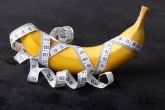 Banana e fita de medição Imagens de Stock Royalty Free