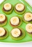 Banana e kiwi affettati con lo sciroppo di fragole sul piatto verde Fotografie Stock