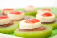Banana e kiwi affettati con lo sciroppo di fragole sul piatto verde Fotografia Stock Libera da Diritti