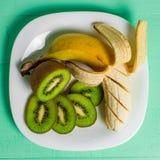 Banana e kiwi su un fondo di legno del piatto Fotografia Stock Libera da Diritti