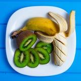 Banana e kiwi su un fondo di legno del piatto Immagini Stock Libere da Diritti