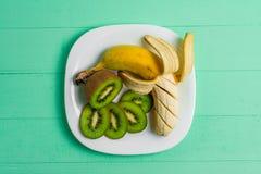 Banana e kiwi su un fondo di legno del piatto Immagini Stock