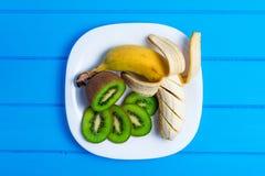 Banana e kiwi su un fondo di legno del piatto Fotografia Stock