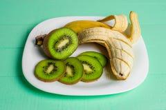 Banana e kiwi su un fondo di legno del piatto Immagine Stock