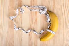 Banana e nastro di misurazione Fotografie Stock