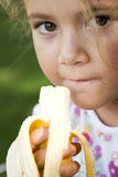 Banana eater. Little girl eating a banana Royalty Free Stock Photos