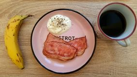 banana eggs bacon and coffee breakfast from above on a wooden ta royalty free stock images