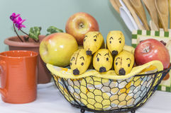Banana Faces Peer from Fruit Basket Stock Images
