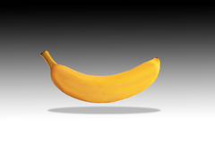 A banana floating in the air with a shadow below. Photo of a banana on a black/white background and lit from above.  The banana is floating above and has a Royalty Free Stock Images