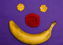 Banana and flowers make happy smile on violet bacgrounf top view flat lay abstract collage stock photos